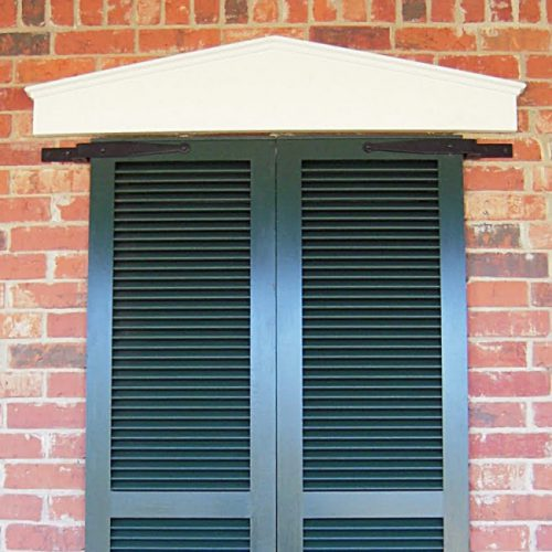 Closeup of Heavy Duty Brick Mount Pintel with black powder coating installed on closed black shutters.