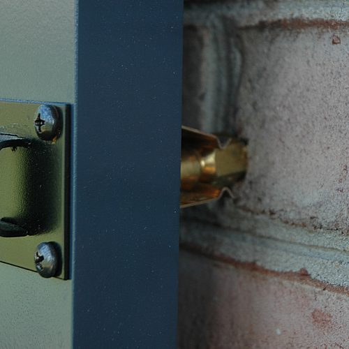 Closeup of installed Bullet Catch on blue shutter and brick.