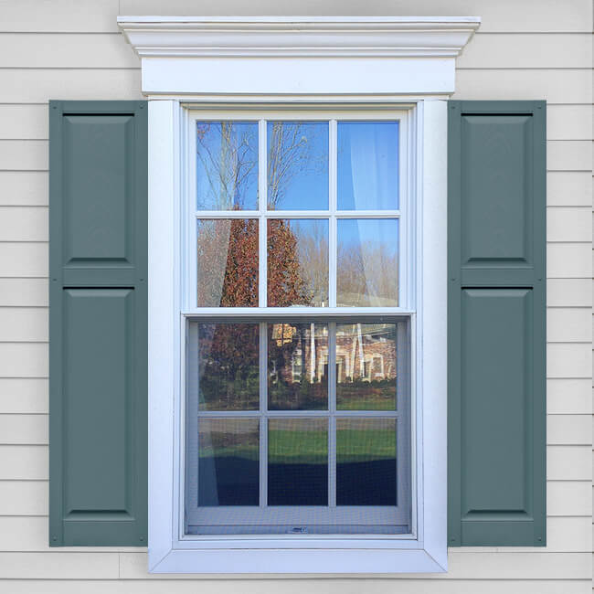 Window with blue vinyl cottage style raised panel shutters in VIN RPC layout.