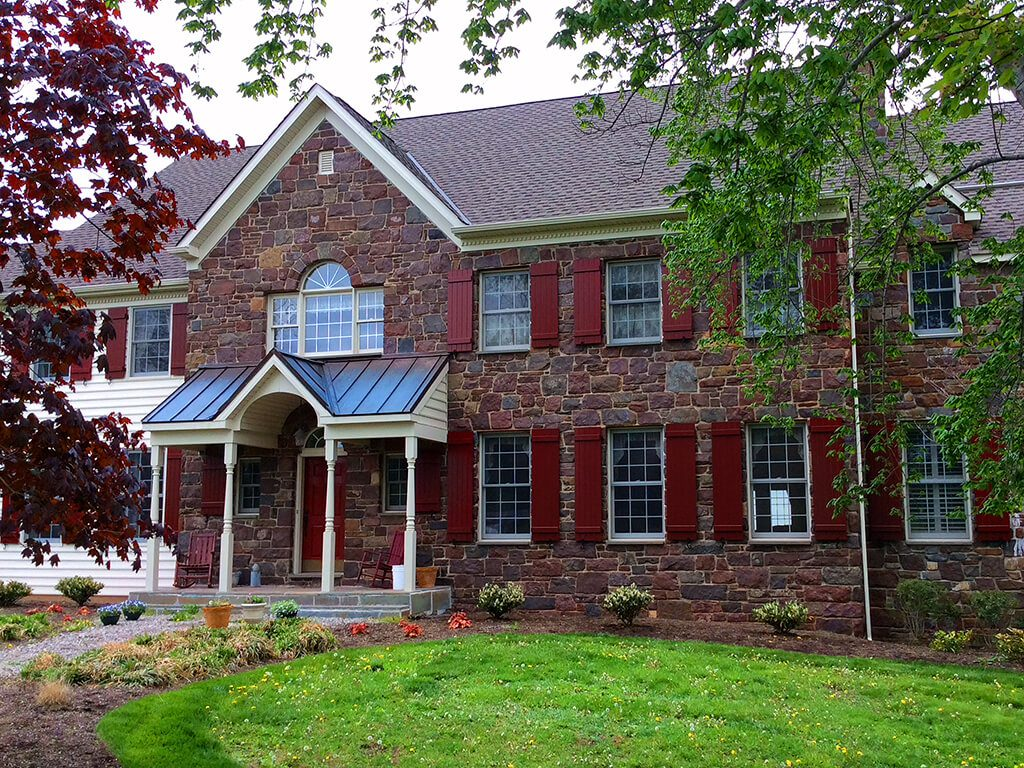 Deep Red Board And Batten Shutters Lend Just The Right Pop Of Color To This Stately