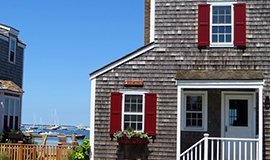 Grey shingle nantucket condo home with red shutters