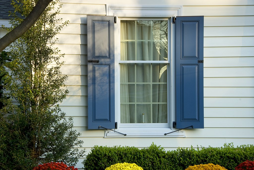 blue panel shutters on white home