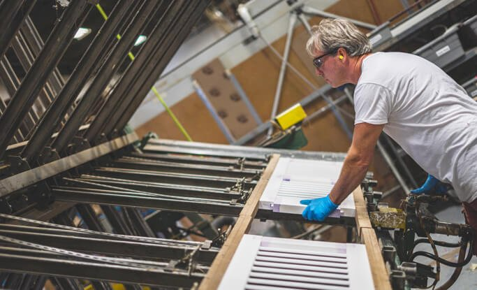 skilled Timberlane artisan handcrafting a set of louver exterior shutters