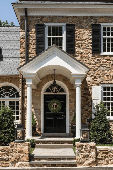 Black louver shutters and white panel shutters surrounding entrance to tan stone farm house