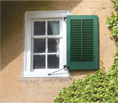 Green louver shutter on historic yellow stucco house