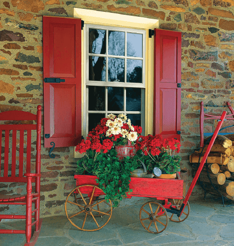 Red panel shutters on red stone wall with red wagon in front