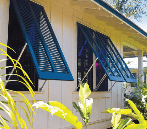 Blue bermuda shutters on white tropical beach house