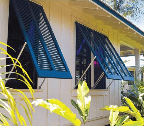 Blue bermuda shutters on white tropical beach house