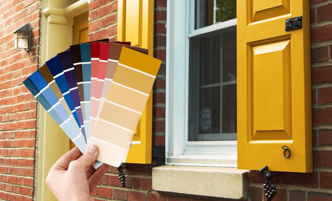 Holding custom yellow color swatch to paint matched yellow Timberlane panel shutters